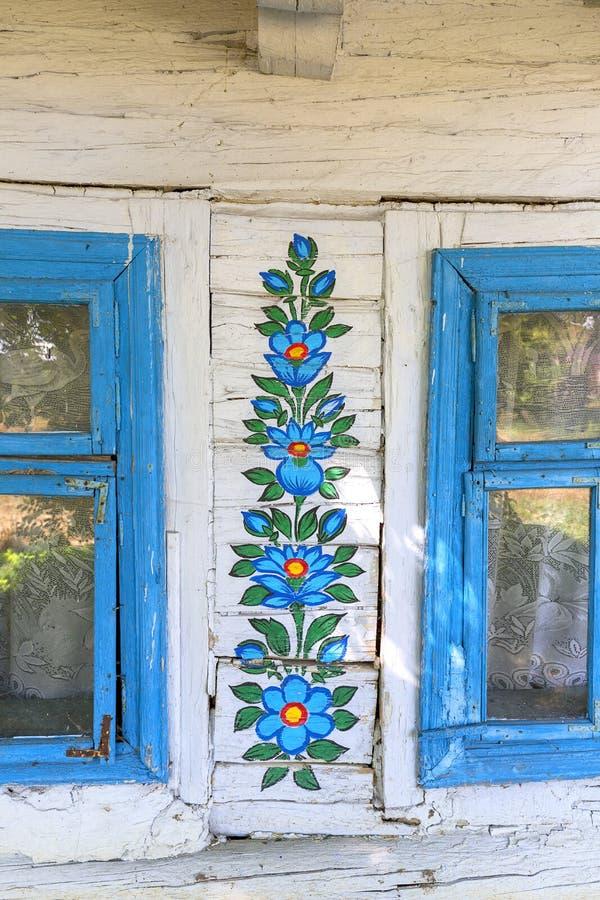 Het geschilderde oude houten die plattelandshuisje met een hand wordt verfraaid schilderde kleurrijke bloemen, Zalipie, Polen stock afbeelding