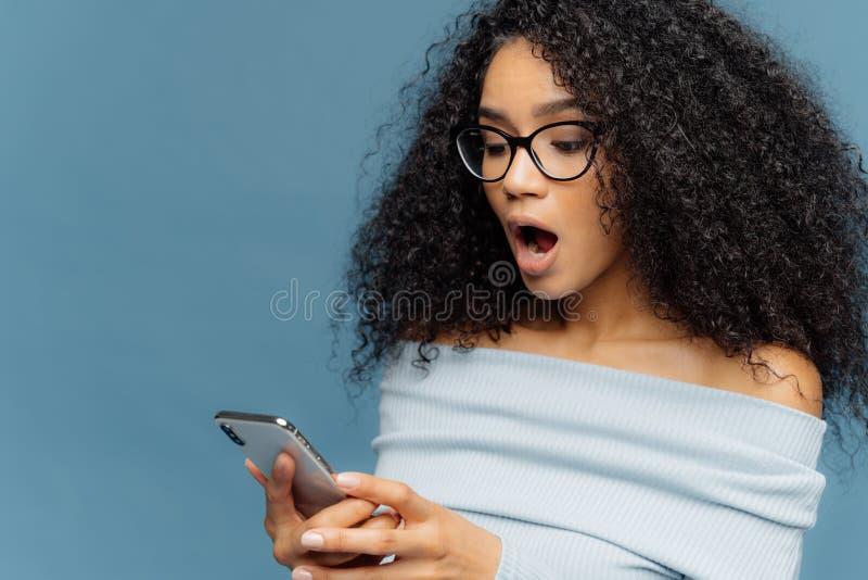 Het geschokte Afrikaanse Amerikaanse vrouwen gots bericht van ex, hijgt van verrassing en de opwinding, leest overweldigend nieuw stock afbeeldingen