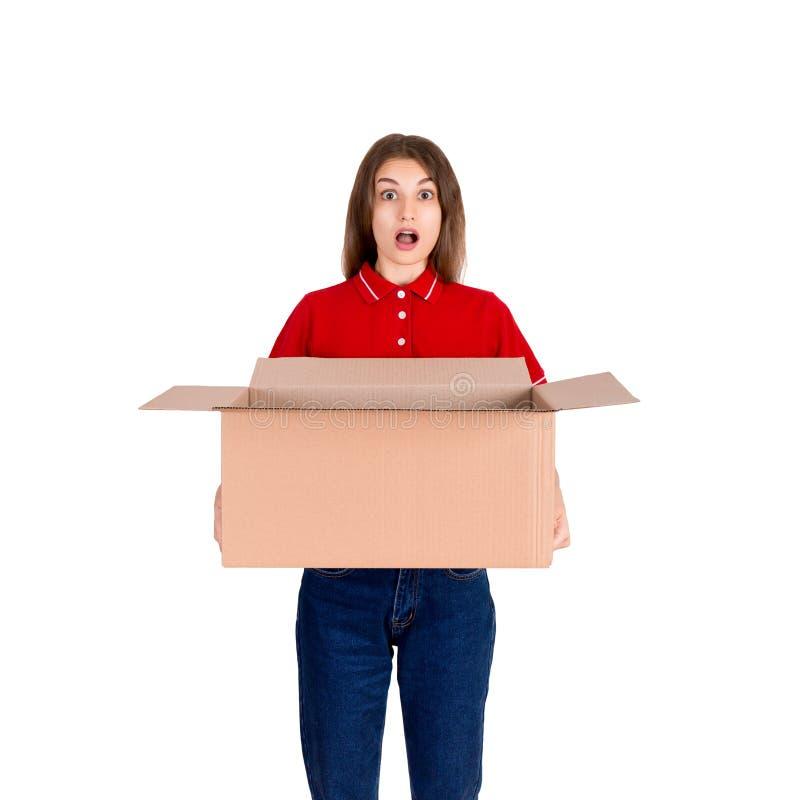 Het geschokte leveringsmeisje houdt een grote open die pakketdoos op witte achtergrond wordt geïsoleerd stock afbeelding