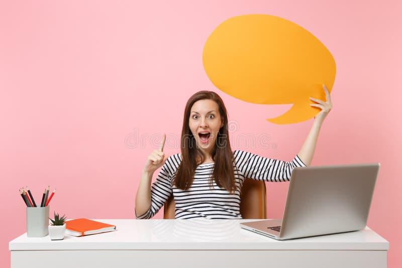 Het geschokte meisje die gele lege spatie houden zegt het de bellenwerk van de wolkentoespraak bij wit bureau met PC-laptop dat o stock afbeelding