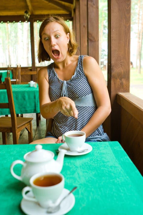 Het geschokte meisje ziet iets in kop thee stock afbeeldingen