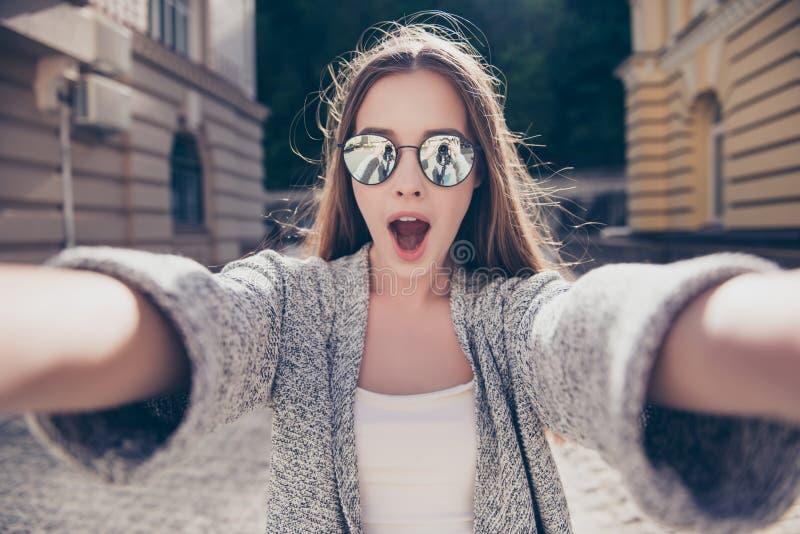 Het geschokte meisje in zonnebril en open mond maakt selfie op a royalty-vrije stock afbeelding