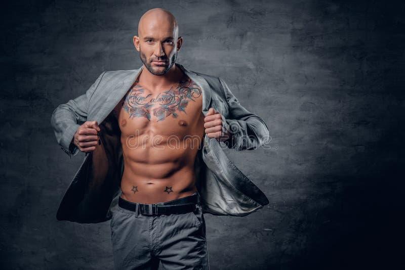 Het geschoren hoofd tatoeeerde mannetje gekleed in een grijs jasje op naakt aan stock foto