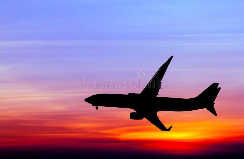 Het gesilhouetteerde commerciële vliegtuig vliegen royalty-vrije stock afbeeldingen