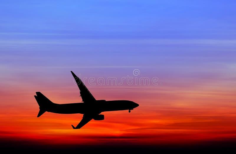 Het gesilhouetteerde commerciële vliegtuig vliegen stock afbeeldingen