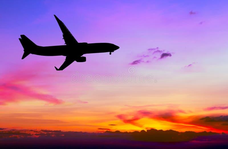 Het gesilhouetteerde commerciële vliegtuig vliegen stock fotografie