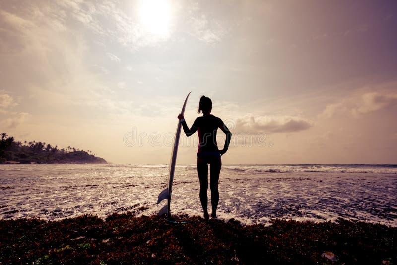 Het gesilhouetteerde jonge meisje van de vrouwensurfer met witte surfplank stock foto's