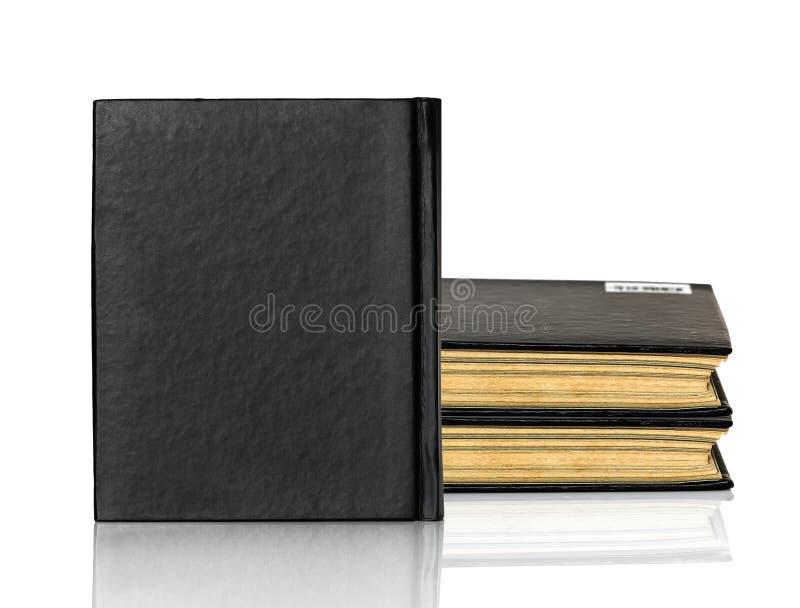 Het gesloten zwarte boek legt op witte achtergrond stock foto's
