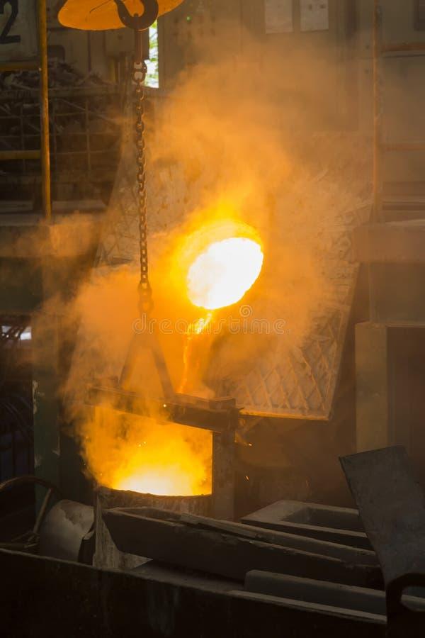 Het gesmolten ijzer gesmolten metaal schonk aan gietlepel in stock fotografie