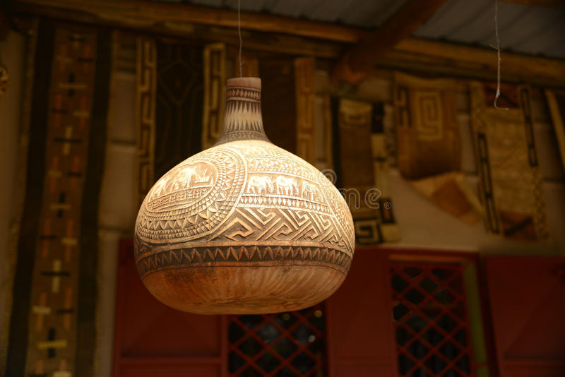 Het gesneden decoratieve Afrikaanse pompoenschip hangen op post stock afbeeldingen