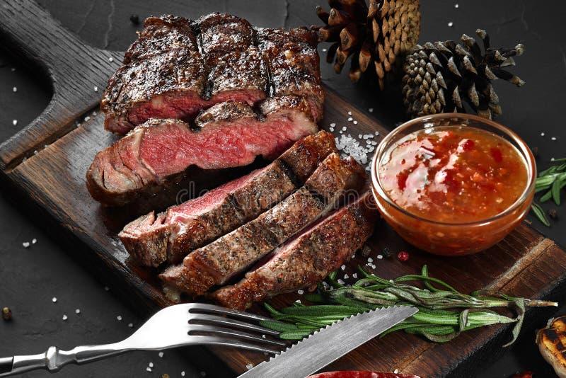 Het gesneden geroosterde middelgrote zeldzame rundvleeslapje vlees diende op houten raadsbarbecue, bbq het haasbiefstuk van het v royalty-vrije stock afbeeldingen