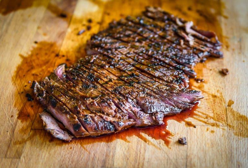 Het gesneden geroosterde sappige gemarineerde lapje vlees van de rundvleesflank op houten raad royalty-vrije stock afbeelding