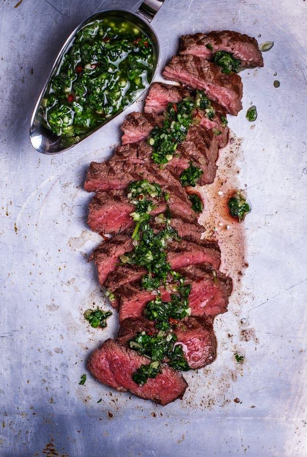 Het gesneden lapje vlees van de rundvleesbarbecue met chimichurrisaus stock foto
