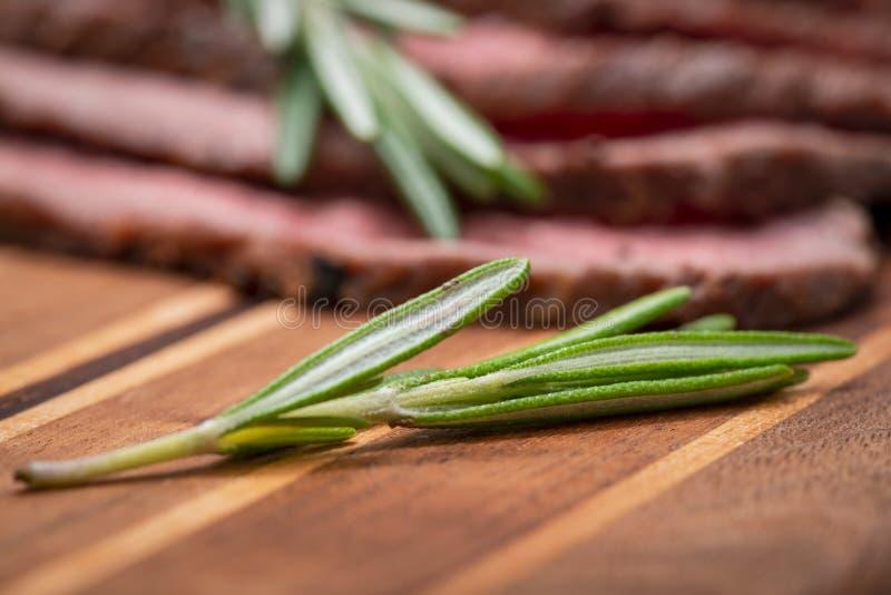 Het gesneden Met gras gevoederde sappige Rundvlees van het Graanbraadstuk dat met Rosemary Fresh Herb op natuurlijke houten scher stock foto