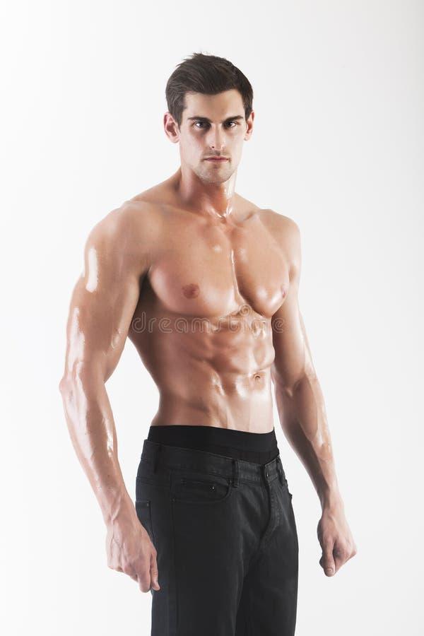 Het gespierde mannelijke model stellen in studio stock foto