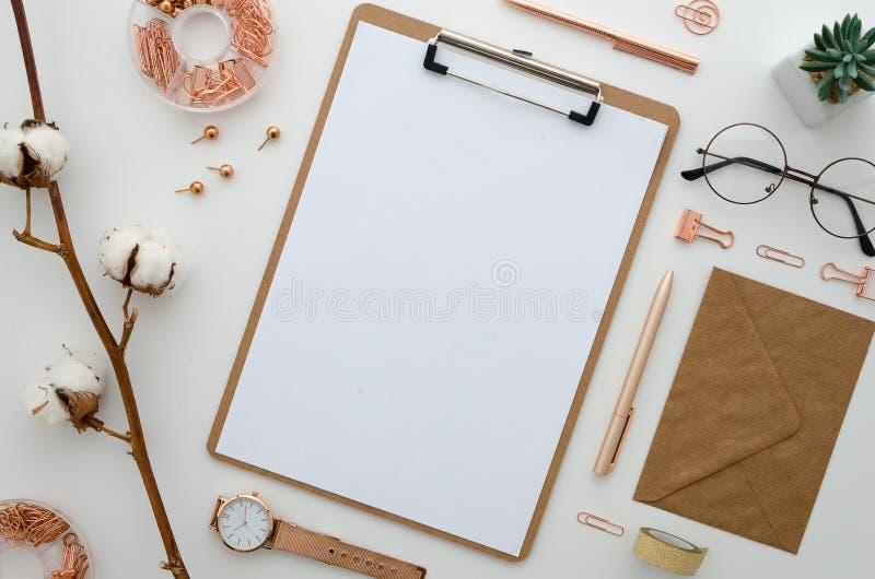 Het gestileerde geschikte klembord van bureautoebehoren, klemmen, polshorloge, glazen, katoenen bloemen, sluit allen in gouden kl stock fotografie