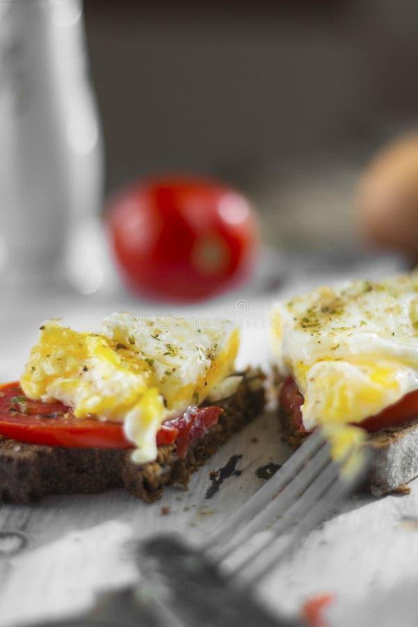 Het gestroopte ei op zuurdesemtoost, met geroosterde tomaten, paddestoelen en salade gaat weg Een gezonde, heerlijke ontbijt of e stock afbeelding