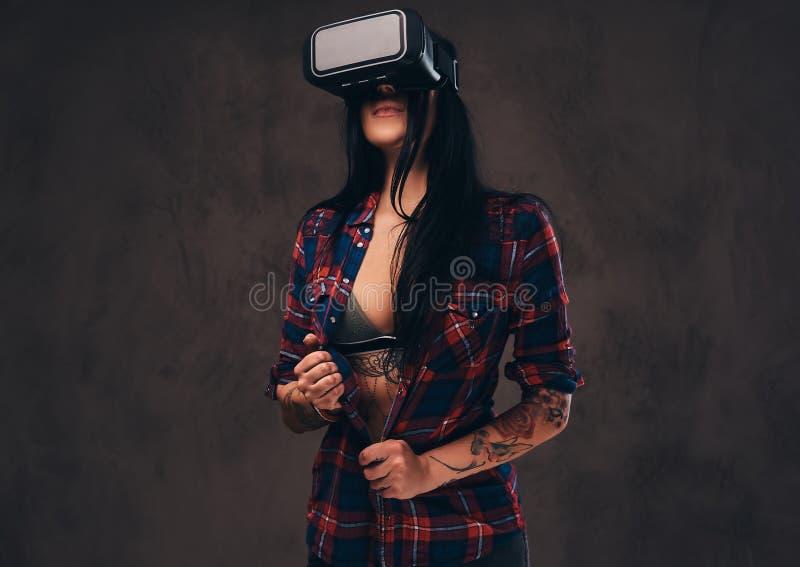 Het getatoeeerde meisje die een rood dragen knoopte gecontroleerd overhemd los die een VR-hoofdtelefoon dragen stock afbeeldingen