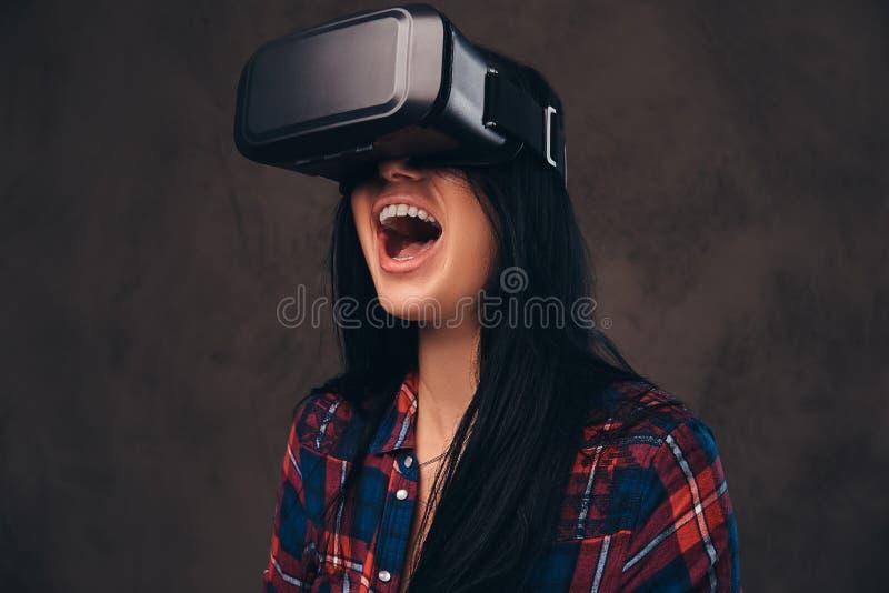 Het getatoeeerde meisje die een rood dragen knoopte gecontroleerd overhemd los die een VR-hoofdtelefoon dragen stock afbeelding