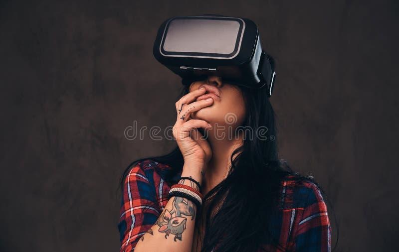 Het getatoeeerde meisje die een rood dragen knoopte gecontroleerd overhemd los die een VR-hoofdtelefoon dragen stock foto