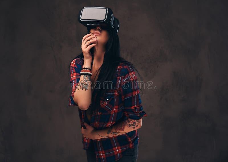 Het getatoeeerde meisje die een rood dragen knoopte gecontroleerd overhemd los die een VR-hoofdtelefoon dragen royalty-vrije stock afbeeldingen