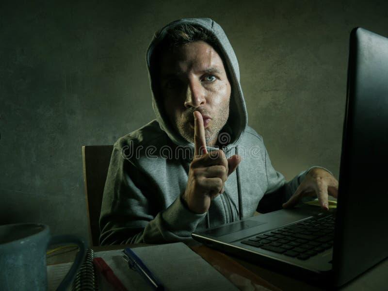 Het gevaarlijke kijken jonge hakkermens in hoodie het typen op laptop computer die en decoderende systeemgegevens of onwettige to royalty-vrije stock foto's