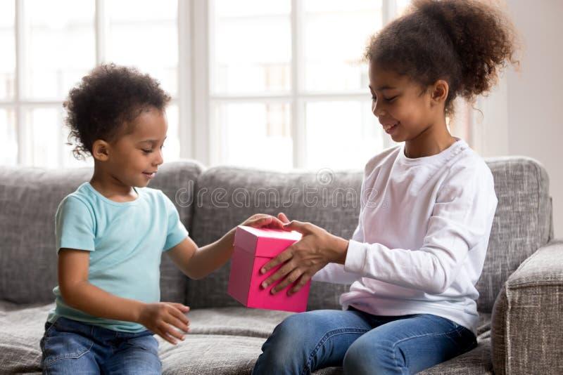 Het geven de Afrikaanse Amerikaanse doos van de meisjes huidige gift aan kleine broer royalty-vrije stock afbeelding