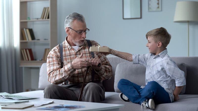 Het geven kleinzoon aanwezige geven aan opa, aandacht en zorg voor gehouden van degenen royalty-vrije stock afbeelding