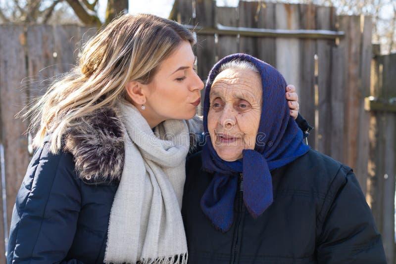 Het geven van een kus aan oma stock afbeelding