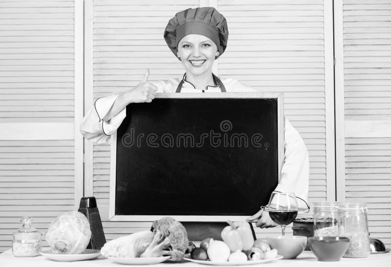 Het geven van haar goedkeuring Mooie vrouwen gesturing duimen omhoog met leeg bord Hoofdkok bij het koken van klasse Belangrijkst royalty-vrije stock foto's