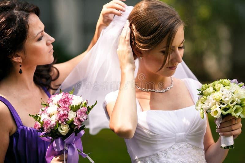 Het gevoelige bruidsmeisje helpt een bruid om op een huwelijkssluier te zetten stock foto
