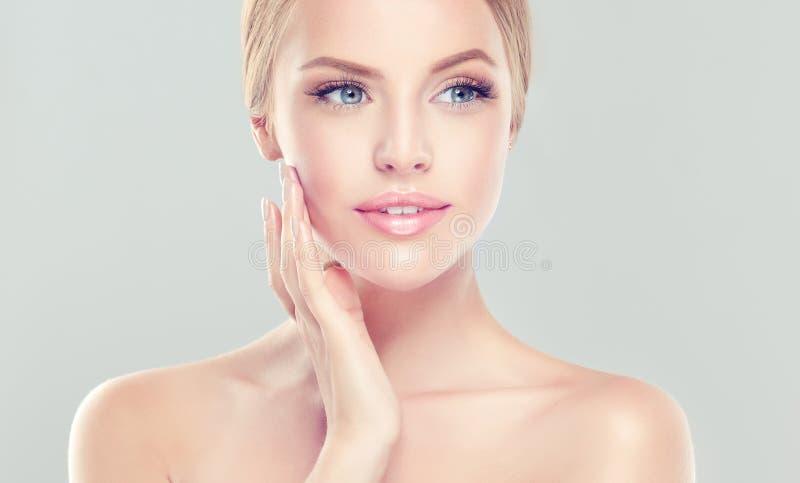 Het gevoelige portret van jonge vrouw met schone verse huid en zacht, maakt omhoog De vrouw raakt teder om gezicht te bezitten royalty-vrije stock foto's