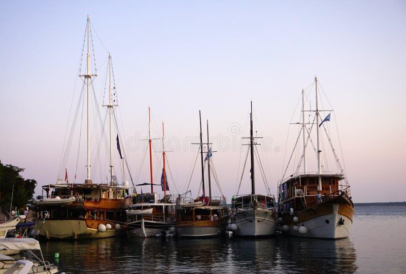 Het gevoerde toerist het varen schepenhoogtepunt van gelukkige toeristen verankerde in haven in het avond blauwe uur royalty-vrije stock afbeeldingen