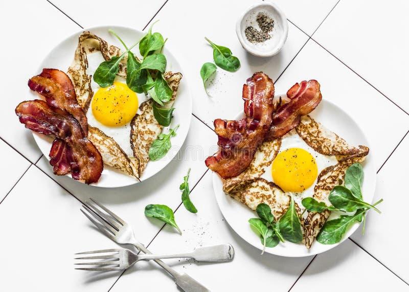 Het gevulde ei omfloerst met bacon en arugula - heerlijke voedzame brunch op een lichte achtergrond, hoogste mening Vlak leg stock fotografie