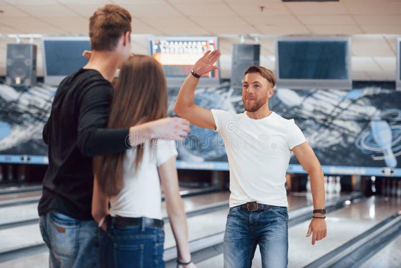 Het is geweldig spel Jonge goede vrienden hebben plezier in bowlingclub in hun weekends stock afbeeldingen