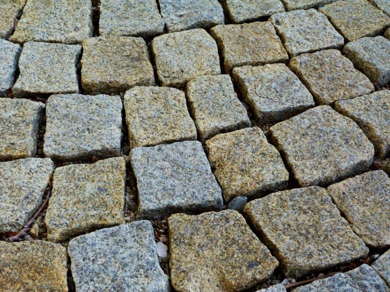 Het geweven en rustieke detail van de de steenbestrating van het kubuskwarts van vierkante vormen plaatste los stock afbeelding