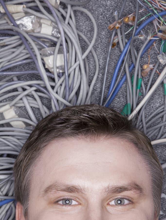 Het gezicht die van de zakenman op computerkabels liggen die half, omhoog eruit zien royalty-vrije stock afbeeldingen