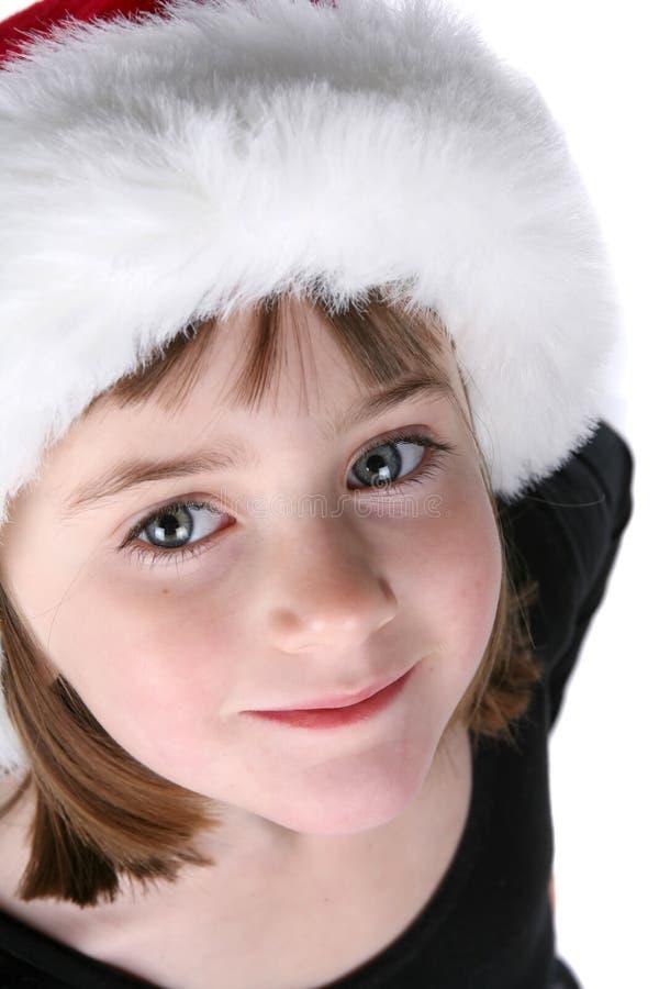 Het gezicht en de ogen van het leuke meisje; het dragen van de hoed van de Kerstman stock foto