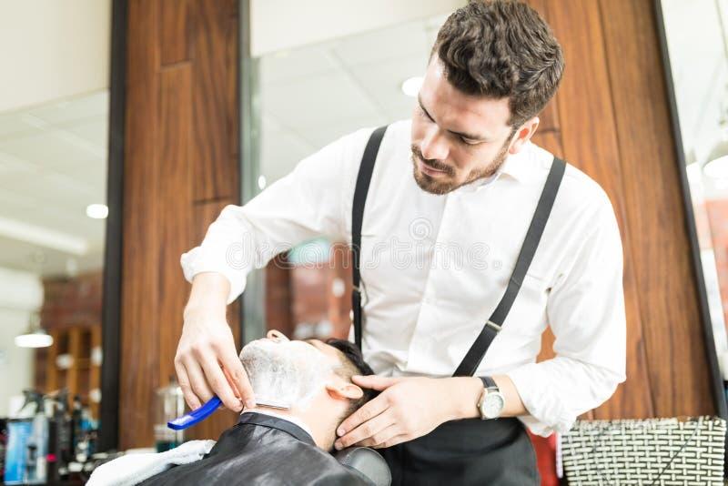 Het Gezicht van Barber Shaving Customer ` s met Blad in Winkel royalty-vrije stock afbeeldingen
