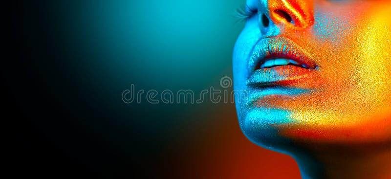 Het gezicht van de mannequinvrouw in heldere fonkelingen, kleurrijke neonlichten, mooie sexy meisjeslippen Het in gloeien gouden  royalty-vrije stock afbeelding