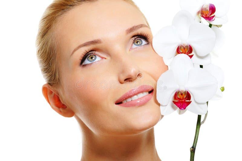 Het gezicht van de mooie het glimlachen vrouw met witte orchidee royalty-vrije stock foto