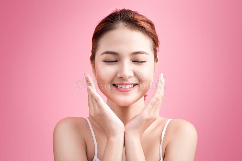 Het Gezicht van de schoonheid Gezichtsbehandeling De jonge Aziatische vrouw met schone perfecte huid raakt haar gezicht stock afbeelding