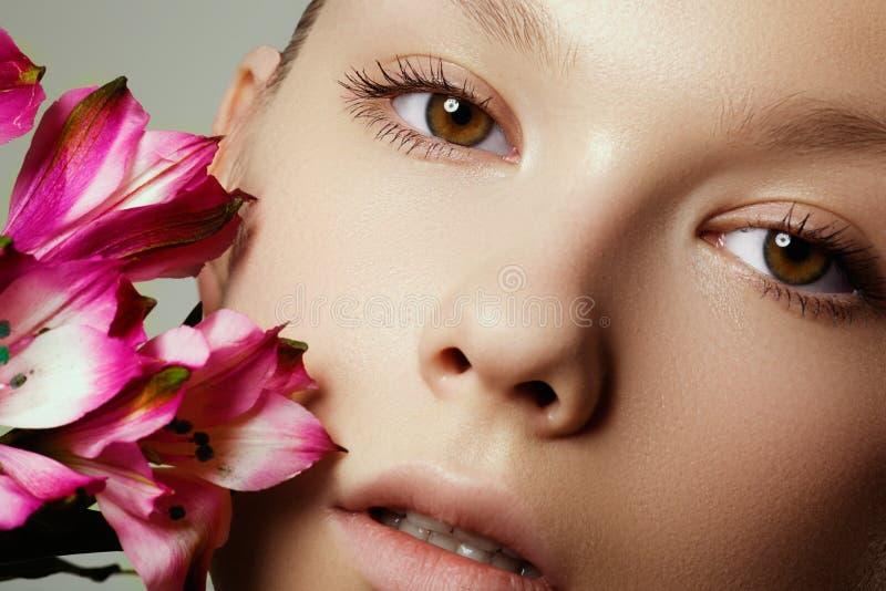 Het gezicht van de schoonheid van de jonge mooie vrouw met bloem Natuurlijke sk stock afbeeldingen