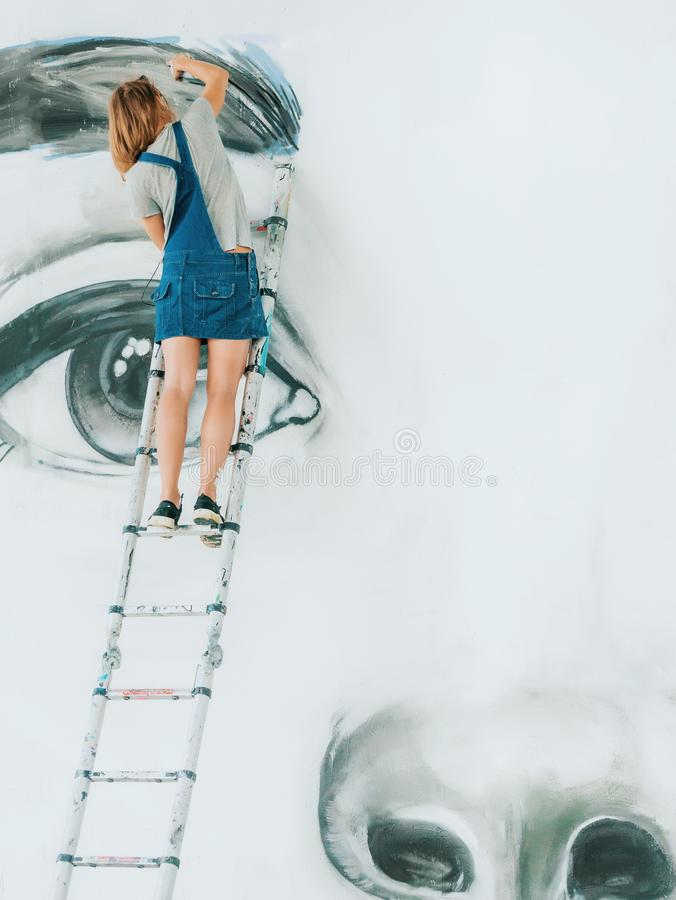 Het gezicht van Drawing van de graffitikunstenaar van mooie vrouw met verf op Straatmuur Wijfje die met borstel werken Stedelijk  stock fotografie