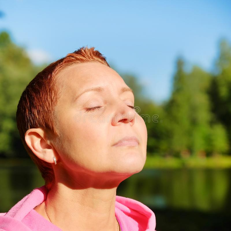 Het gezicht van het meisje in de zon De gezondheid en de energie zijn een concept harmonie van lichaam en aard royalty-vrije stock afbeelding
