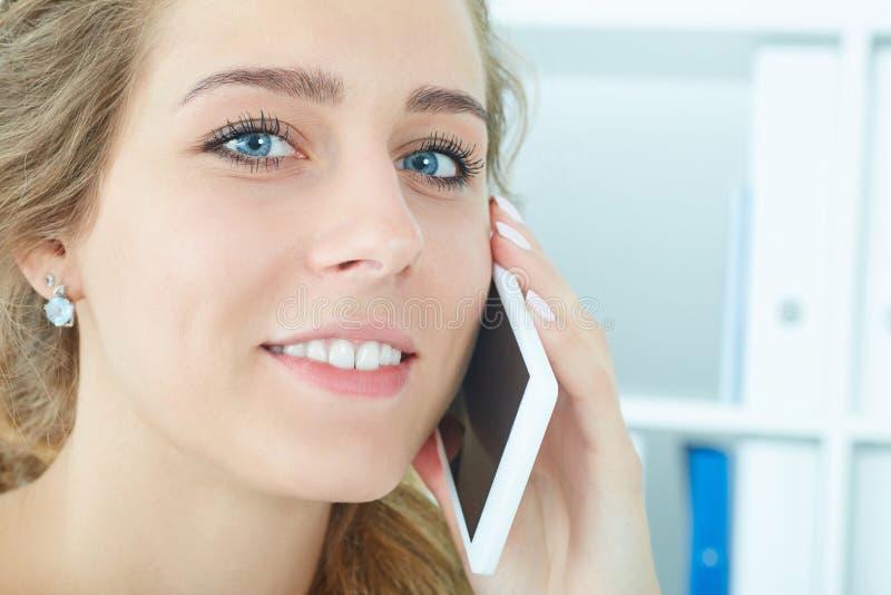 Het gezicht van het mooie glimlachende jonge meisje die op de mobiele telefoon in het bureau spreken stock fotografie