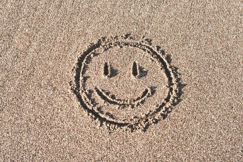Het gezicht van Smiley dat op strandzand wordt getrokken stock fotografie