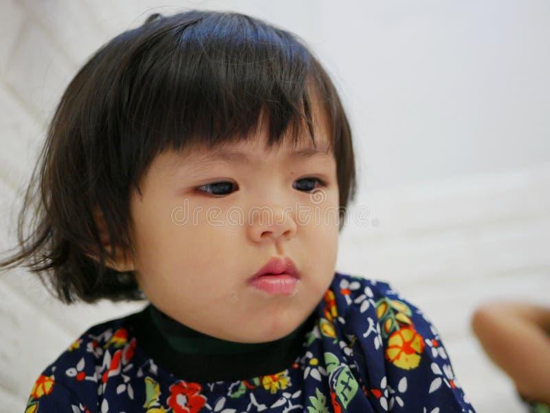 Het gezicht van weinig babymeisje, 2 jaar oud, terwijl het letten op/het staren bij een smartphone stock fotografie