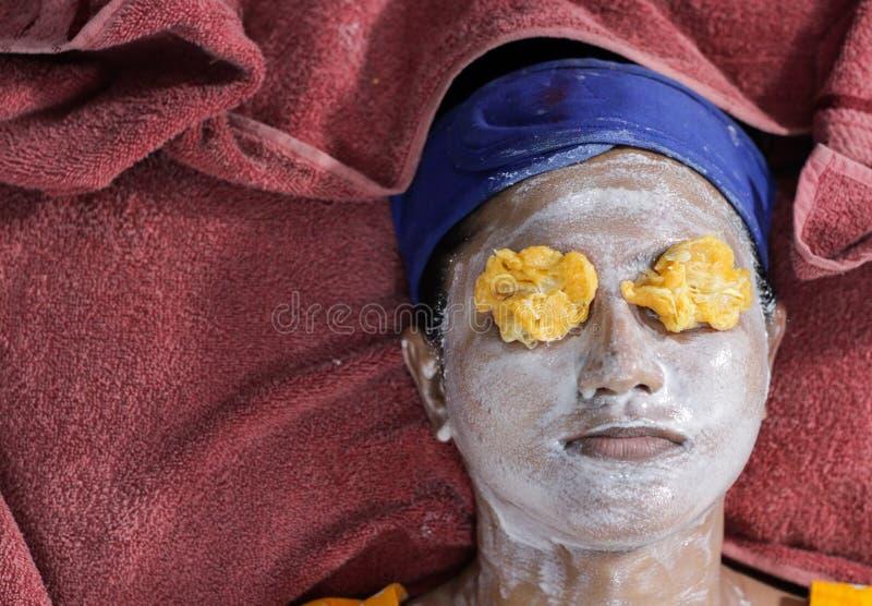 Het gezichtsdiepakmasker was op gezicht van een dame met haarband van toepassing met ogen met oranje pulp worden gesloten kruiden royalty-vrije stock afbeelding
