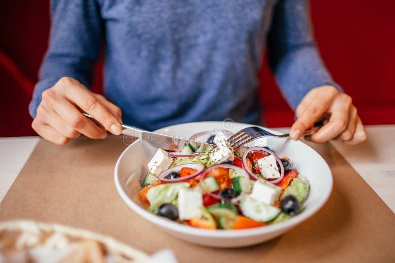 Het gezond eten, op dieet zijn en mensenconcept - sluit omhoog van jonge vrouw die plantaardige Griekse salade thuis op houten et royalty-vrije stock foto